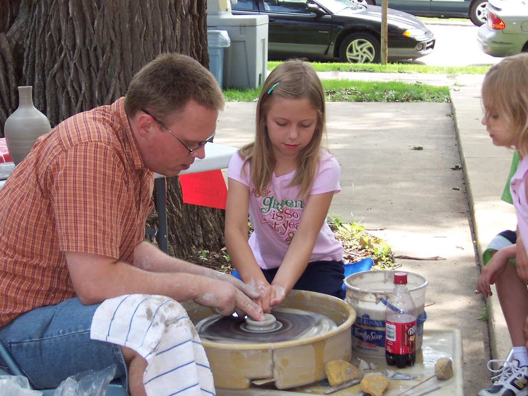 Tyler, the potter, showing children how to make pottery at the Blanden Art Museum in Fort Dodge, Iowa
